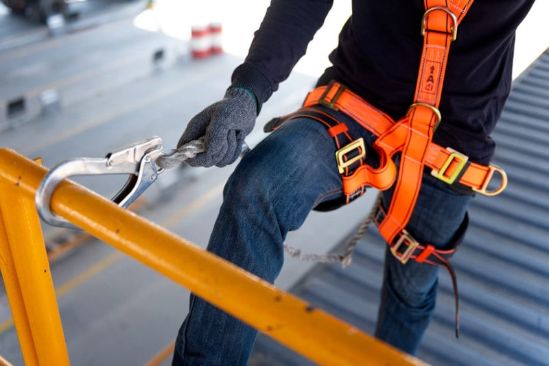 Roofer roof construction worker wearing safety harness